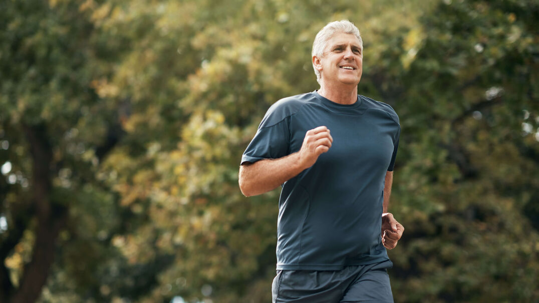 A fit older man goes running in a park.