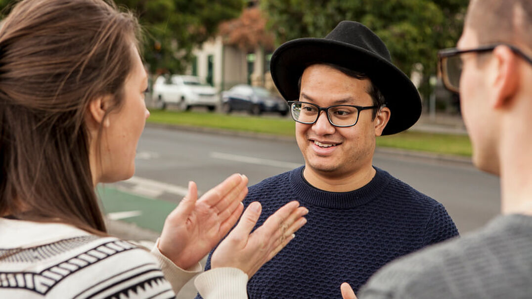 Two young men and a young woman are having a conversation in Auslan. One of the young men who is wearing a fashionable wide-brim hat is looking amused at what the woman is signing.